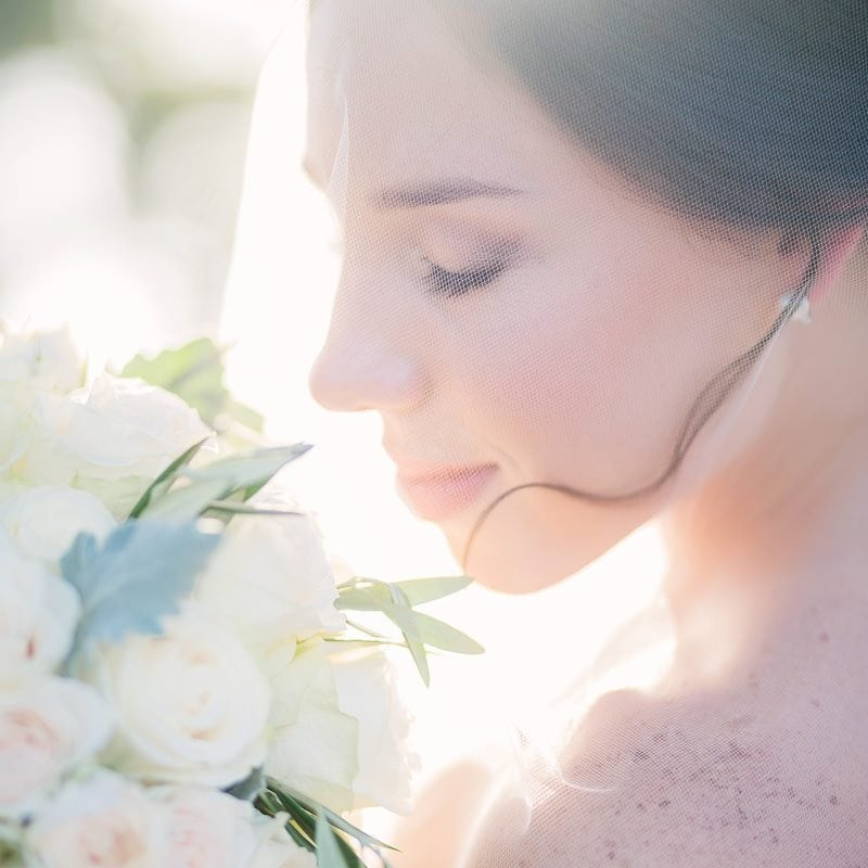 Bride looks at her flowers as sunlight backlights her