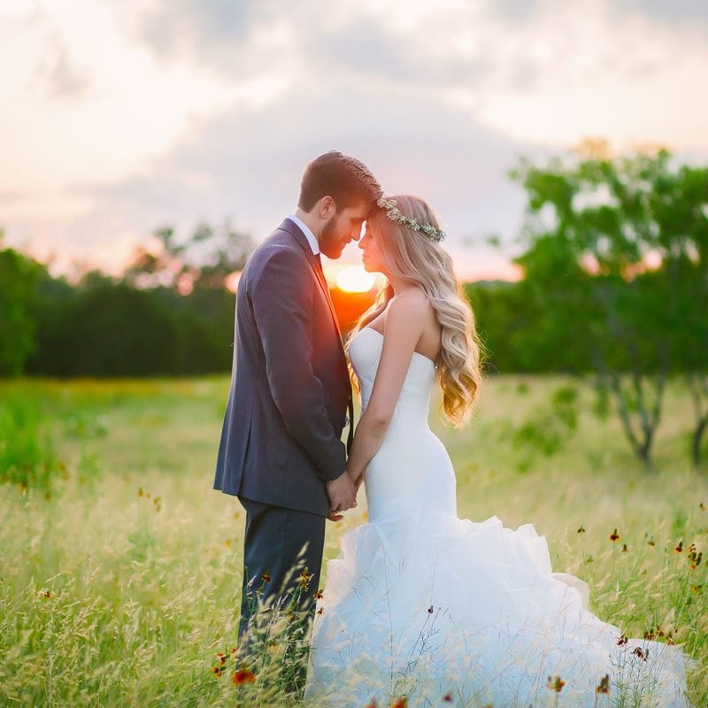 Bride and groom tap foreheads together at sunset in a field