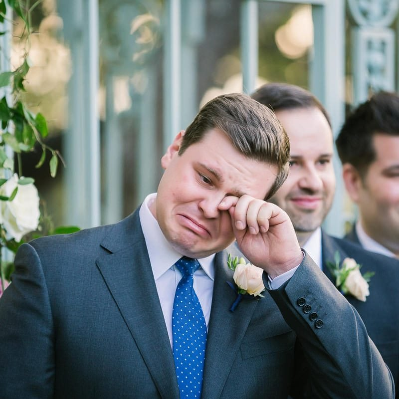 groom wipes tear from his eye as his bride walks down the aisle