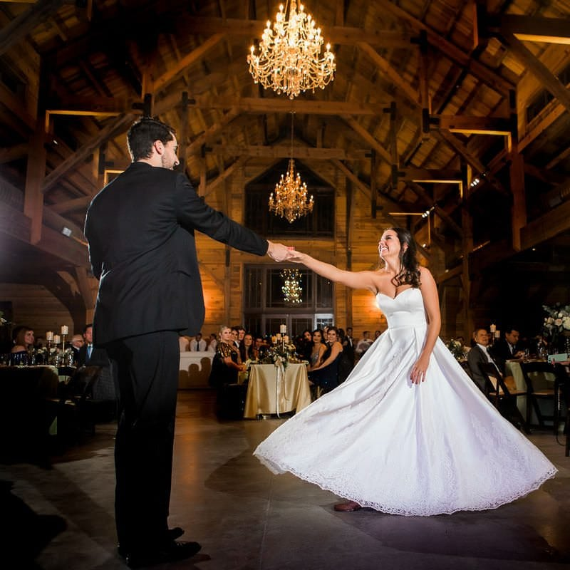 Groom twirls his bride as they share their first dance