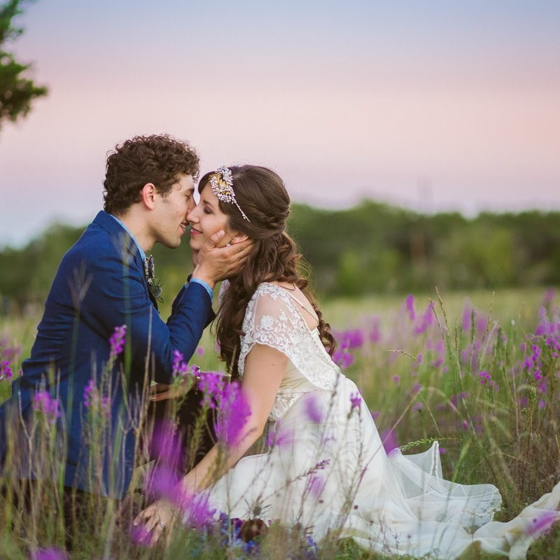bride and groom kiss in a field of bluebonnets at sunset