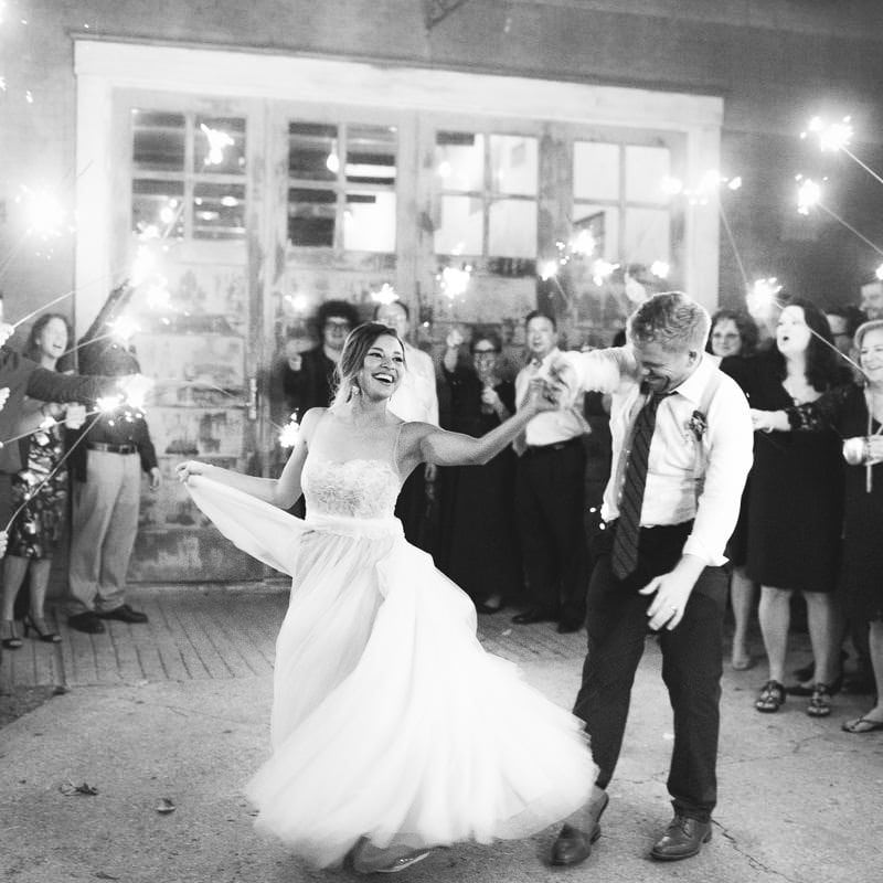 groom twirls his bride as they exit reception surrounded by guests holding sparklers
