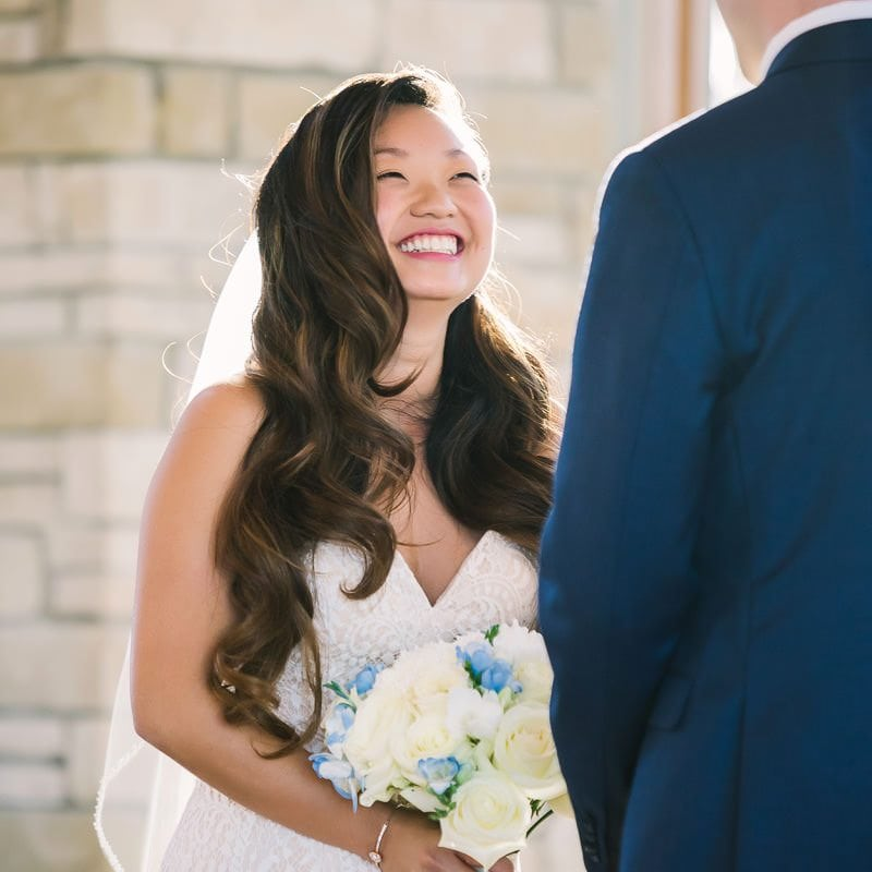 bride smiles at groom at their wedding ceremony