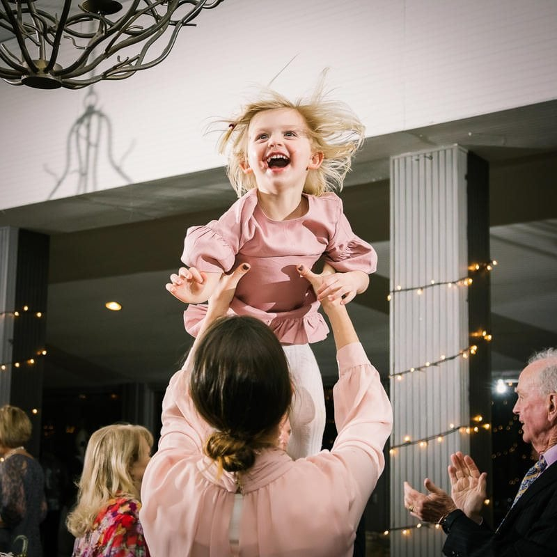 Father tosses his daughter in the air at wedding reception as she laughs