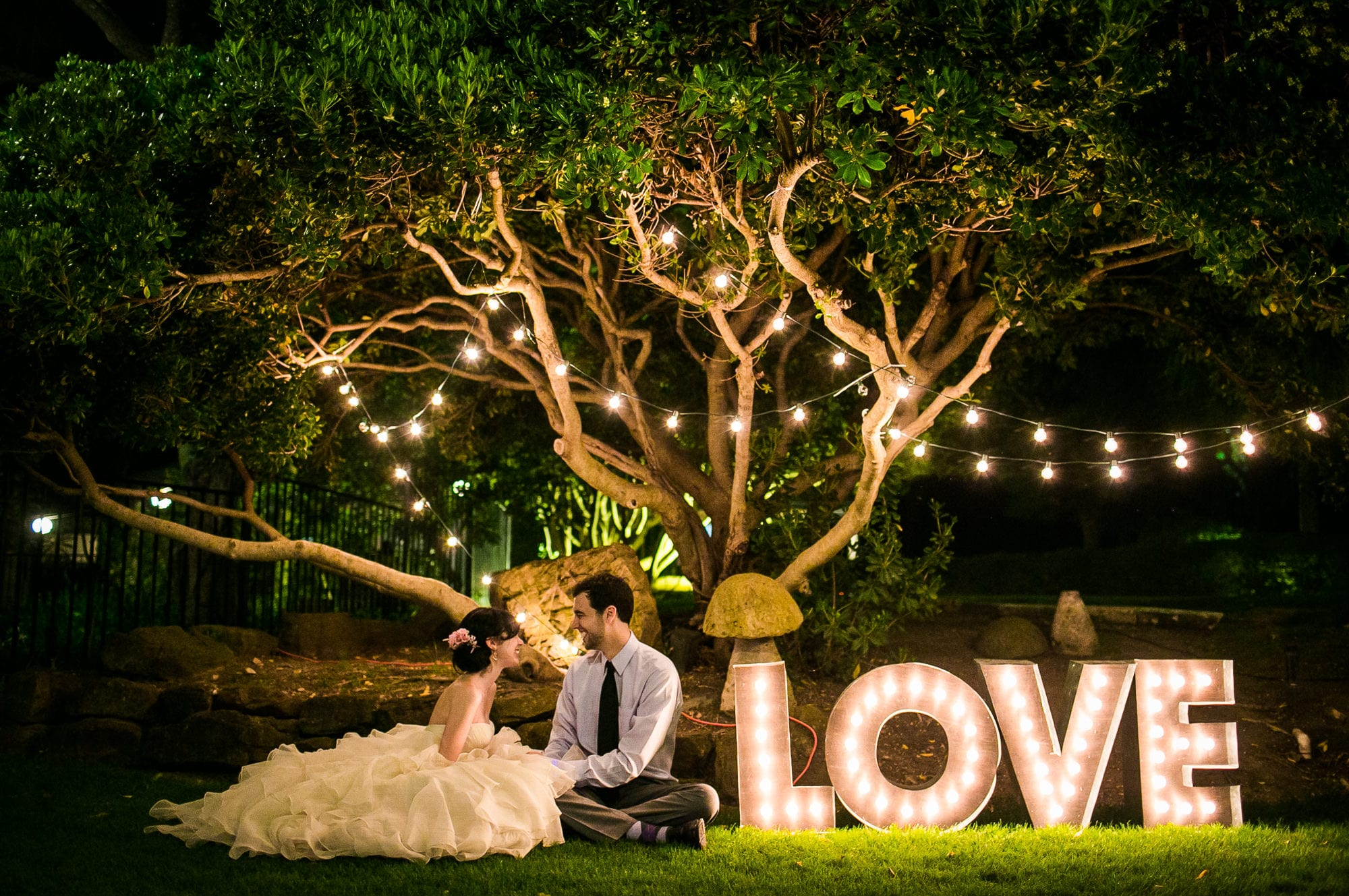 bride and groom sit at night in front of sign that says love