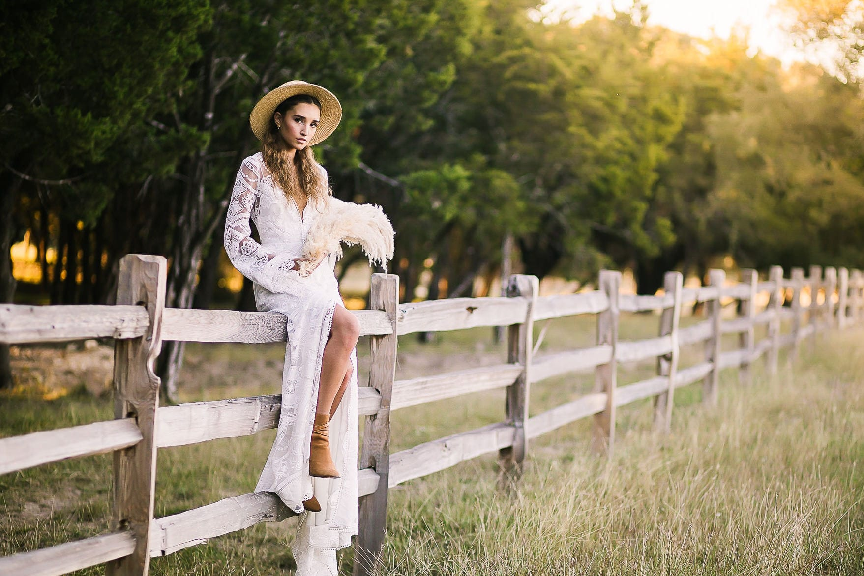 Woman in hat sits on fence