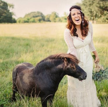 Bride laughs while standing next to a horse, Austin wedding photography