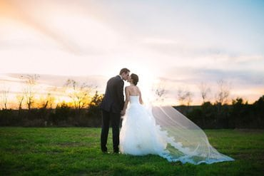 Bride and groom share a kiss as they watch the sun set on the horizon
