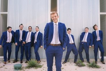 Groomsmen do their best impression of groom while he laughs